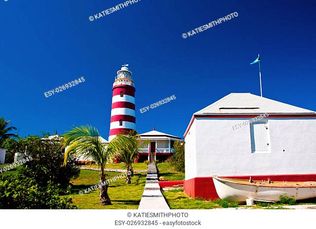 Red and white candy cane striped lighthouse on Elbow Cay, Abaco, Bahamas, Hope Town. Storage shed with small boat are in the foreground