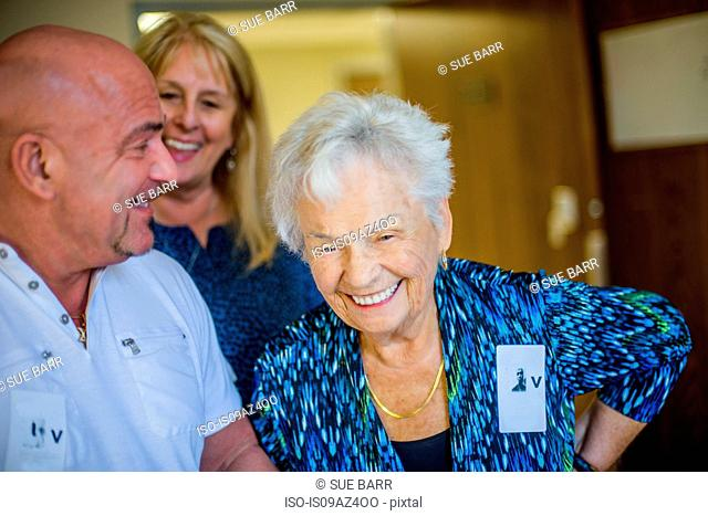 Gray haired woman with friends laughing