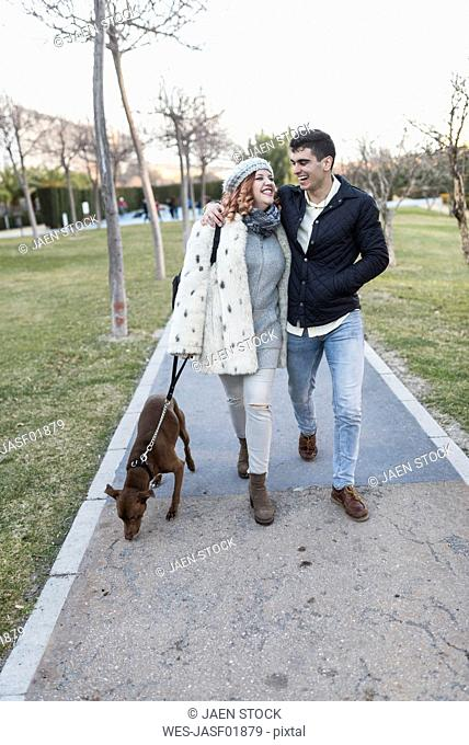 Happy young couple strolling with the dog