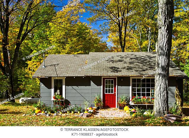 A cottage in the forest with fall foliage color along Highway 119 in Michigan's Lower Peninsula, USA