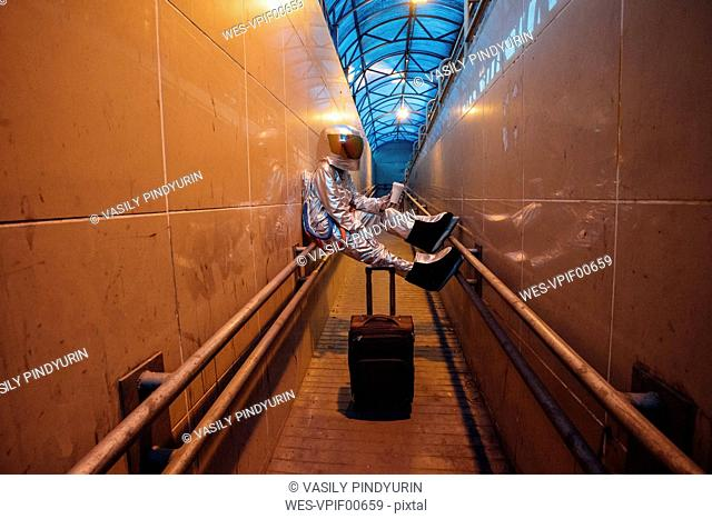 Spaceman in the city at night with rolling suitcase in narrow passageway