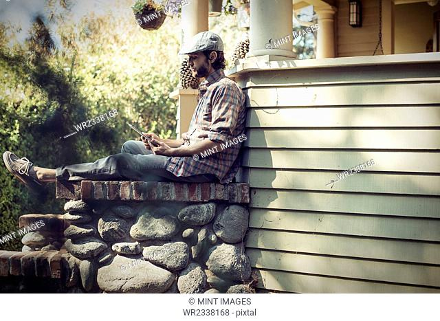 A man sitting relaxing in a quiet corner of a porch, using a digital tablet
