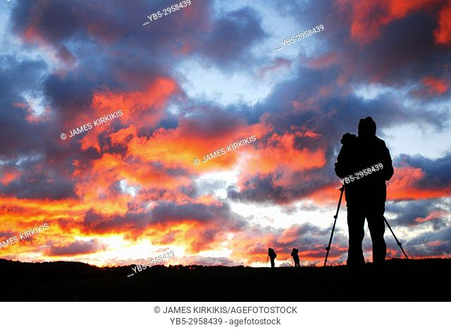 A male photographer sets up his tripod to capture a glorious sunrise
