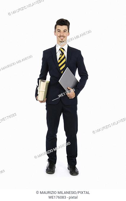 Businessman standing in the studio with computer and documents under his arms, he is wearing a black suit, a striped tie and white shirt