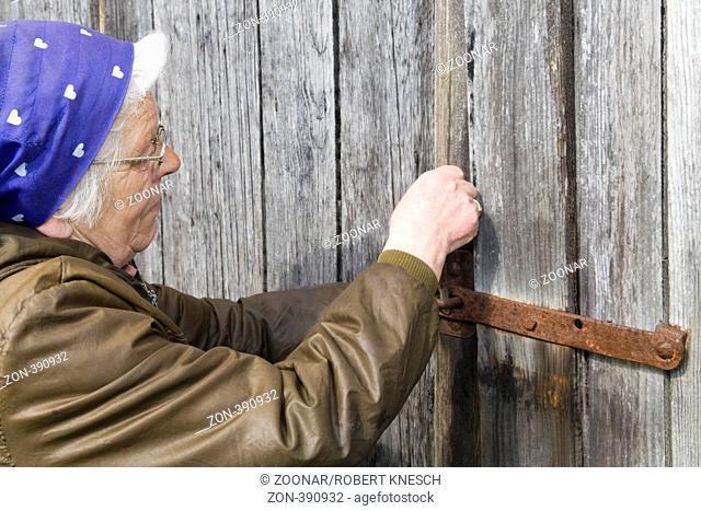 Frau in ihren Siebzigern mit Kopftuch schließt den Riegel am Scheunentor auf ihrem Bauernhof