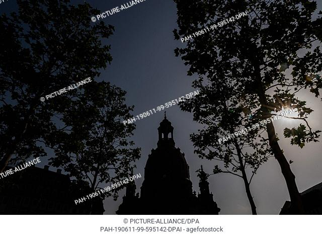 11 June 2019, Saxony, Dresden: The Frauenkirche can be seen as a silhouette in the morning between two trees on the Neumarkt