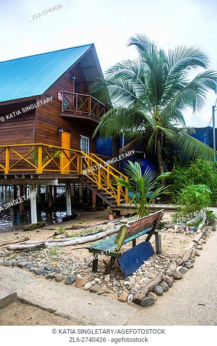 Two story Brown house on high stilts with wrapped around porch, an old bench is around the house. This house is in the water in Bastimentos Island