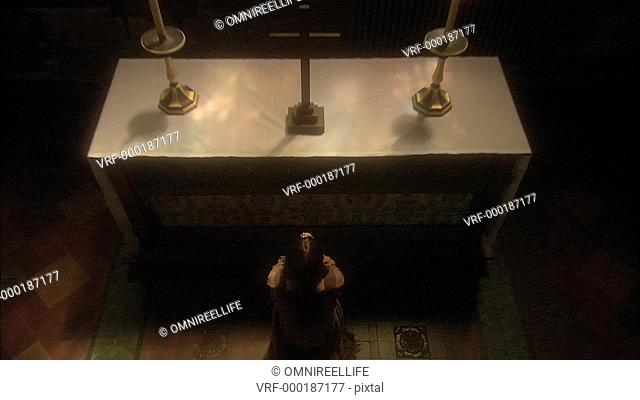 Joan of Arc kneeling and praying in front of alter with crucifix and candles and stained glass windows behind