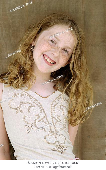 Preteen girl with long gold-brown hair and freckles, smiling at camera, head tilted to side, waist up, against brown wood background