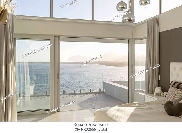Sunny, tranquil modern luxury home showcase interior bedroom with ocean view