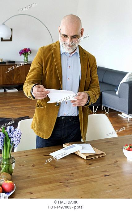 Mature man reading letter by table at home