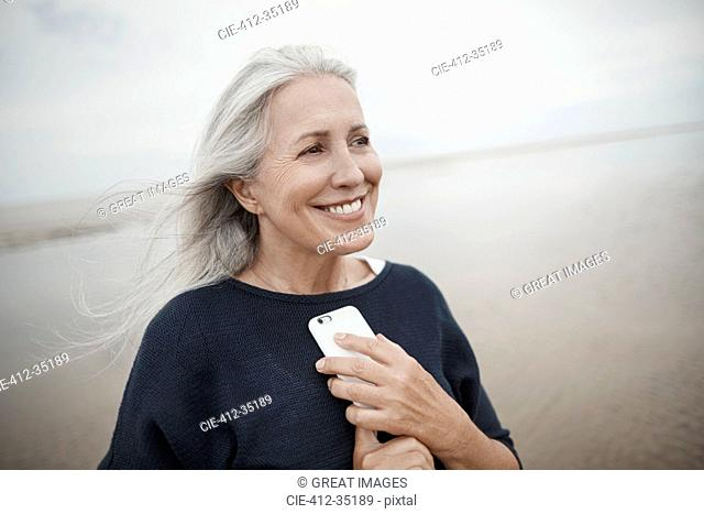Smiling senior woman holding cell phone on winter beach