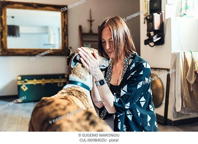 Young woman petting her dog in apartment