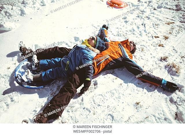 Italy, Val Venosta, Slingia, happy father and son lying in snow
