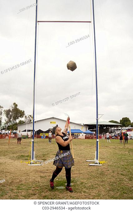"""A kilted young woman competes in the """"""""Sheaf Toss"""""""" at a Scottish festival in Costa Mesa, CA, using a pitchfork to toss a 16-pound burlap bag of straw over a..."""
