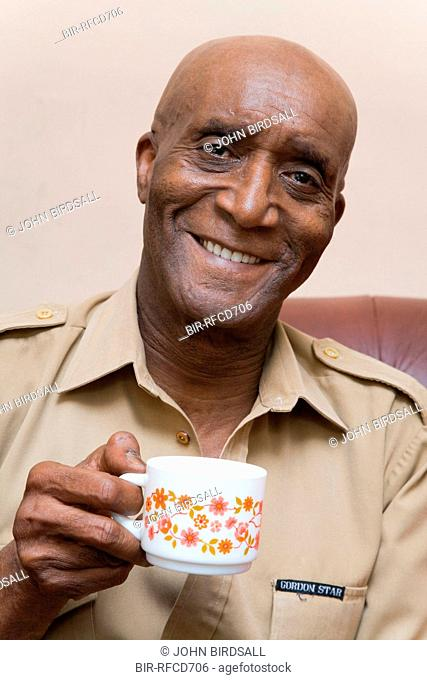 Older man sitting at home enjoying a cup of coffee
