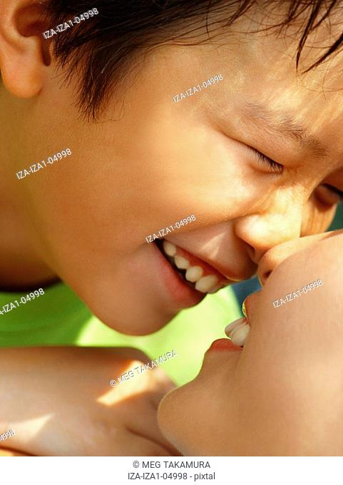 Close-up of a mother face to face with her son and smiling