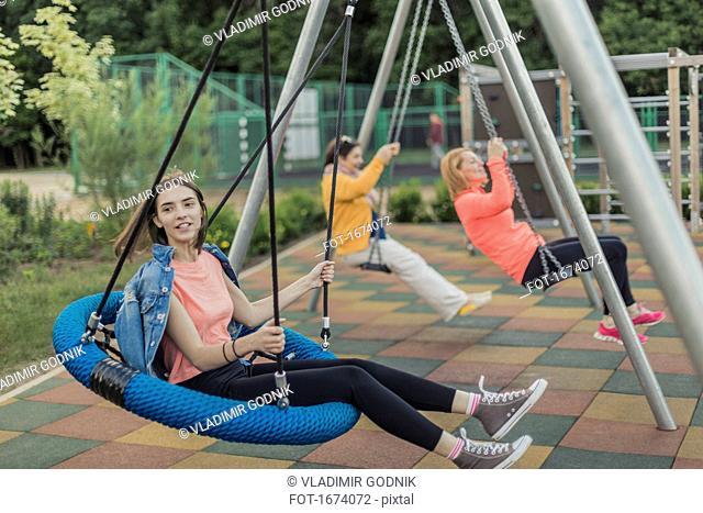Full length of happy women swinging on swing at playground