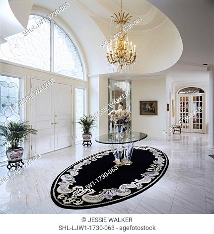 ENTRY HALLS: marble floor, double door, chandalier, white, large arched stained glass windows and sidelights, black oval area rug beneath glass entry hall table