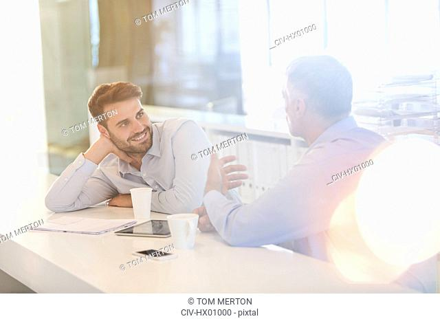 Businessmen with digital tablet and coffee talking in office