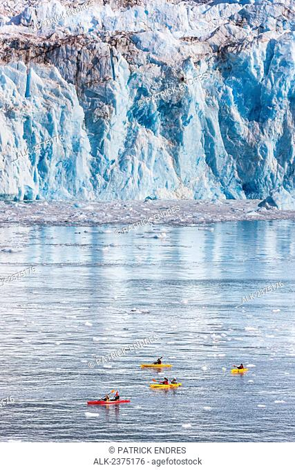 Sea Kayakers paddle in Barry Arm, near the face of Cascade glacier, Prince William Sound, southcentral, Alaska