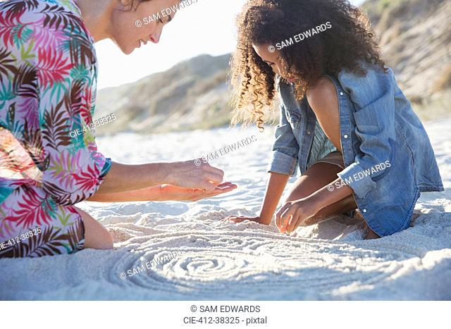 Mother and daughter drawing spirals in sand on summer beach