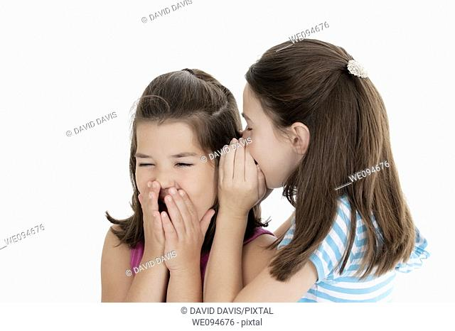 Two Caucasian girls telling secrets on white background