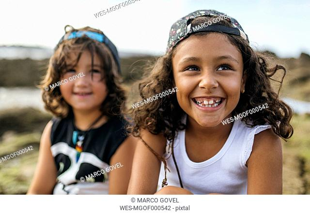 Spain, Gijon, portrait of smiling little girl and her friend in the background sitting at rocky coast