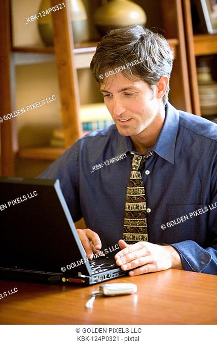 Man using laptop computer in the study of his home