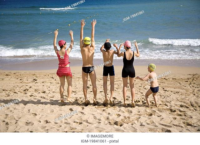 Five children standing on the sand with arms outstretched
