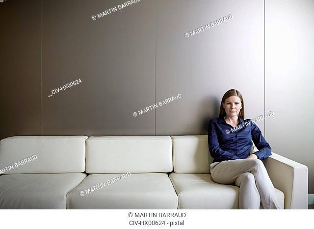 Portrait confident businesswoman with legs crossed on sofa