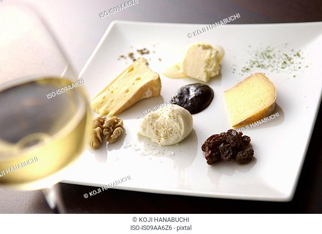 Still life with white wine and selection of cheeses