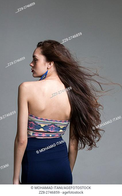 Rear view of a slender young woman with long dark hair looking away
