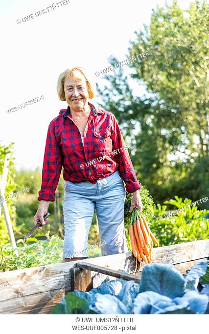 Smiling senior woman at vegetable patch
