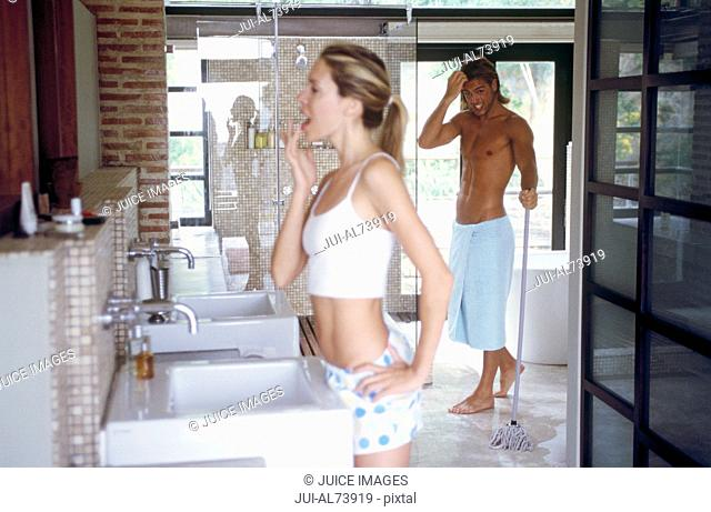 View of a young woman brushing her teeth while her boyfriend dries off after a shower