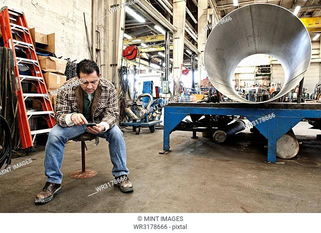 Hispanic man factory worker checking a part inventory on his cell phone in a sheet metal factory