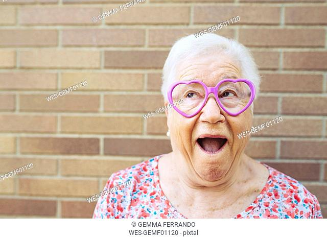 Portrait of senior woman wearing heart-shaped glasses pulling funny faces