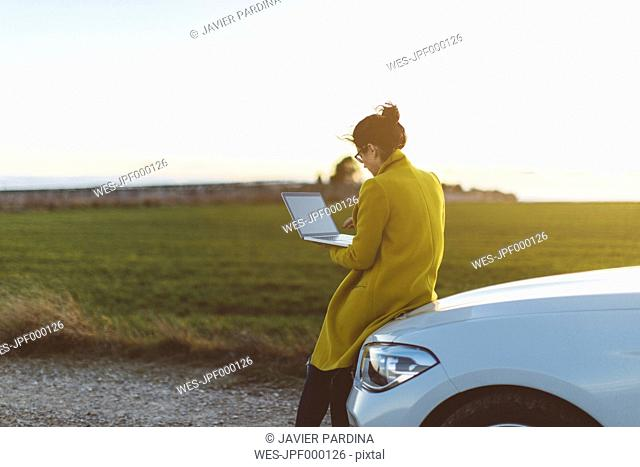 Woman using laptop at car