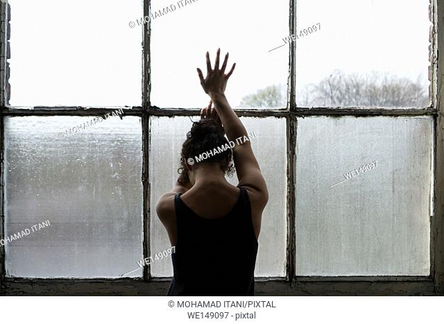 Rear view of a young woman standing by the window hands touching the glass