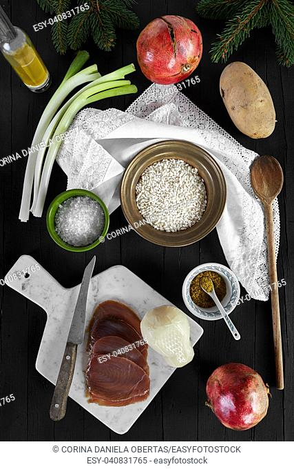 Ingredients for the risotto recipe with scamorza cheese and smoked tuna fish. Photographed from above, on a black wooden background