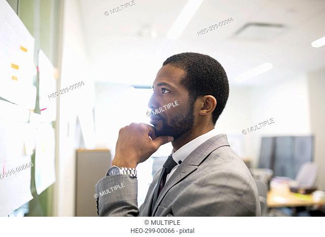 Pensive businessman reviewing hanging paperwork in office