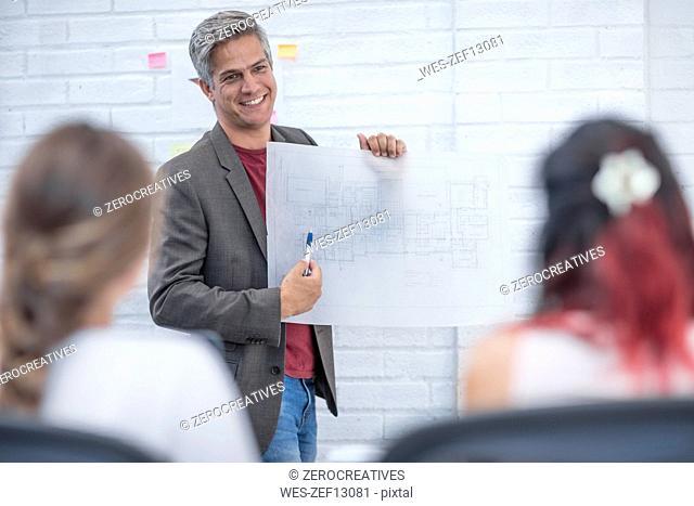 Businessman showing plans at a presentation