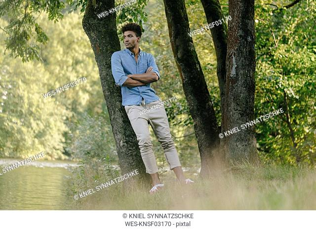 Young man in park leaning against a tree at the water