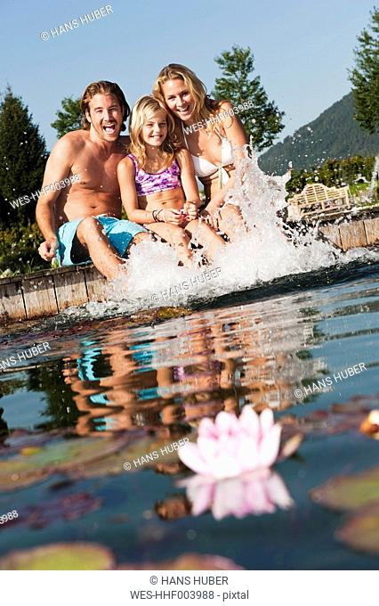 Austria, Salzburg County, Family sitting on bridge over natural pool