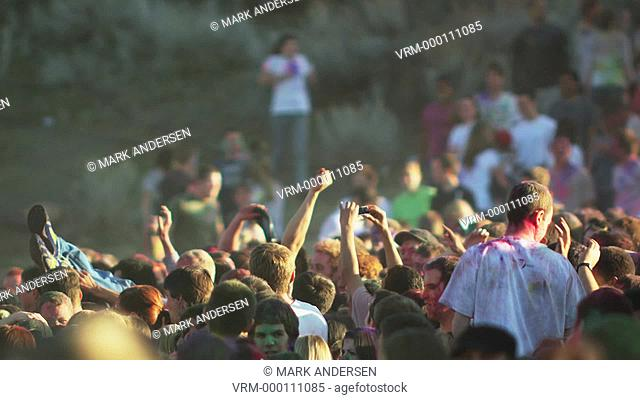 crowd of people at a Hindu festival throwing a young man into the air