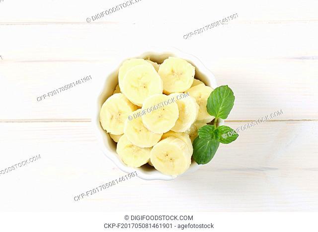 bowl of sliced banana on white background