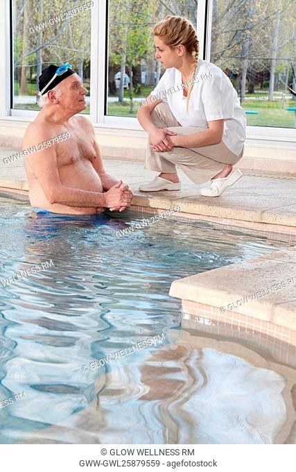 Man in a swimming pool and talking to a health worker