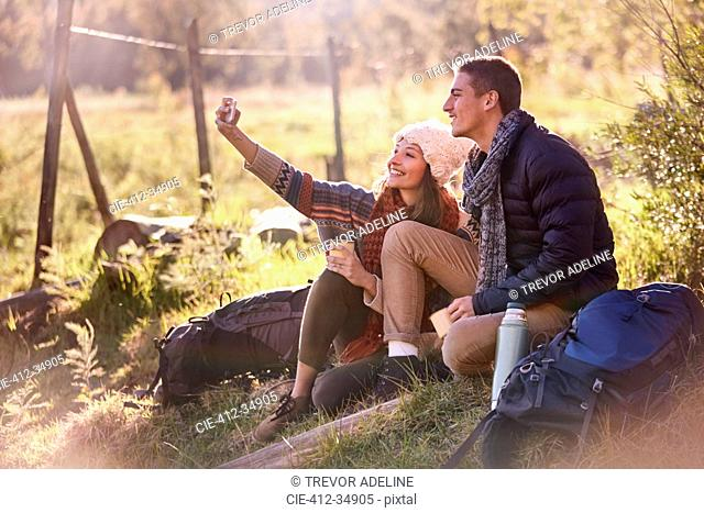 Young couple taking a break from hiking, taking selfie with camera phone