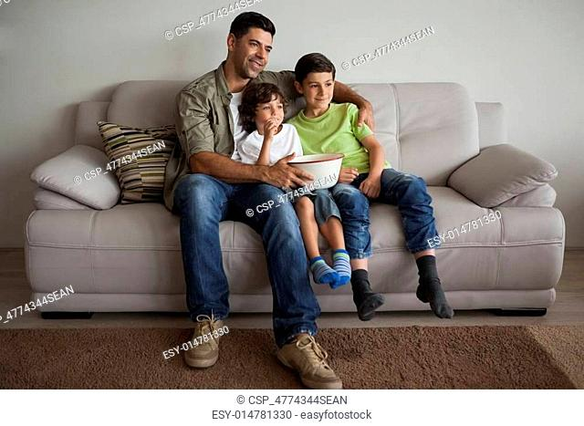 Full length of a happy father and sons with popcorn bowl watching tv in the living room at home