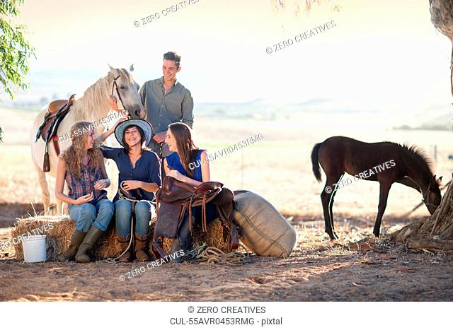 Four young friends sitting on hay bale with horses